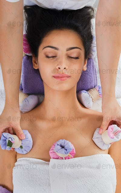 Woman has herbal ball massage in ayurveda spa wellness center