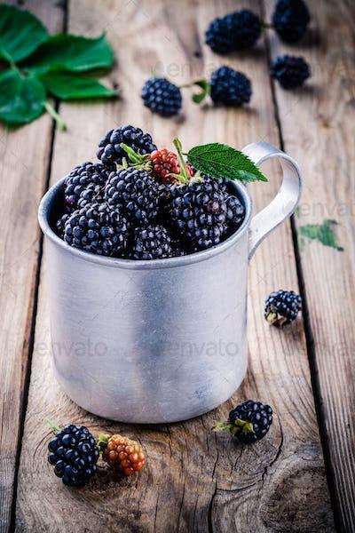 juicy fresh organic blackberries in old mug