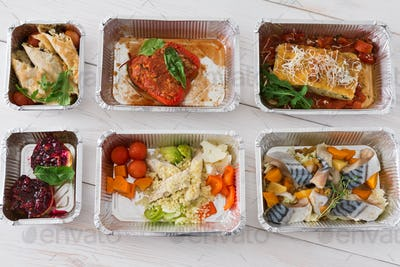 Healthy food take away in boxes, top view on wood