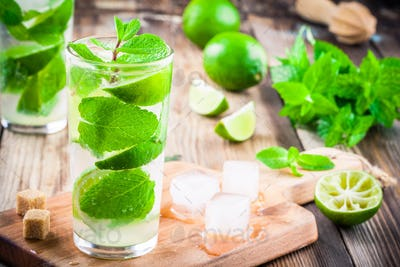 fresh cocktails with lime, mint and ice in glass
