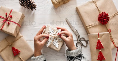 Woman's hands wrapping christmas holiday present with craft twine