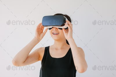 Happy young woman in VR headset looking away