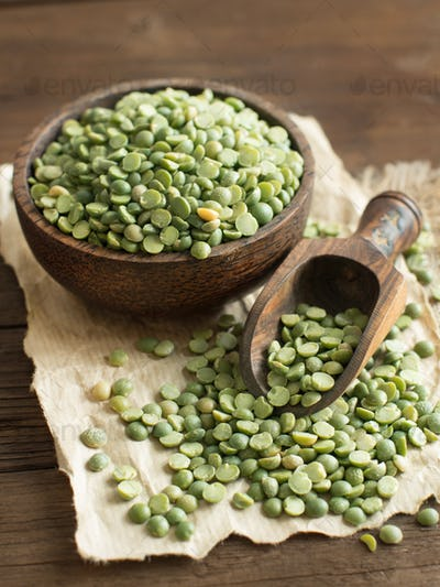 Uncooked Green Split Peas in a bowl  with a spoon