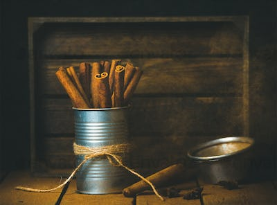 Cinnamon sticks in tin can, rustic wooden background, copy space