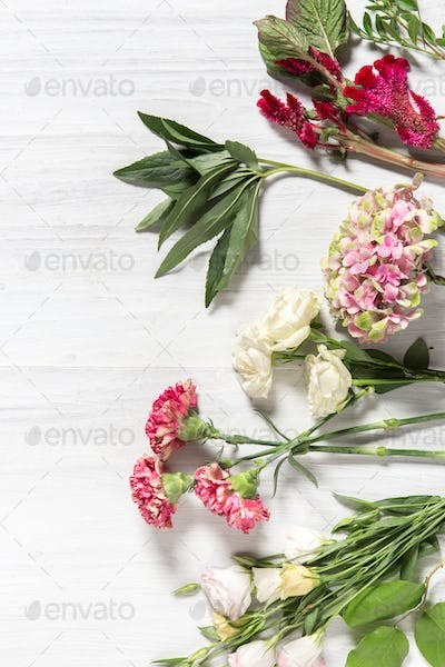 The flowers on white wooden background