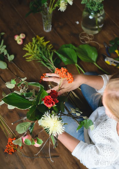 florist make a bouquet of flowers and branches