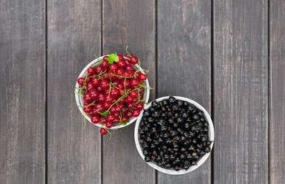 Black and red currants in bowl on rustic wood background
