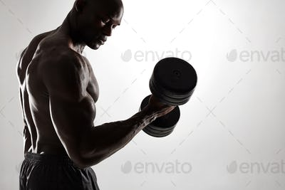 Muscular young bodybuilder exercising with dumbbells