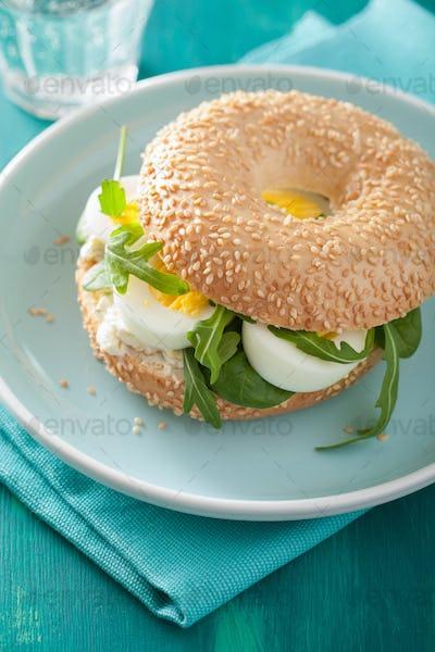 breakfast sandwich on bagel with egg cream cheese arugula