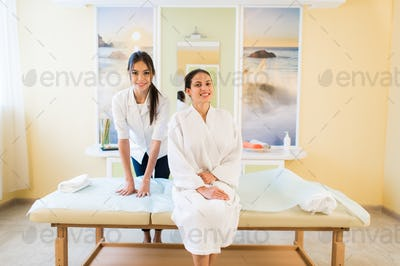 Woman beautician doctor with patient in spa wellness center. Young female professional cosmetologist