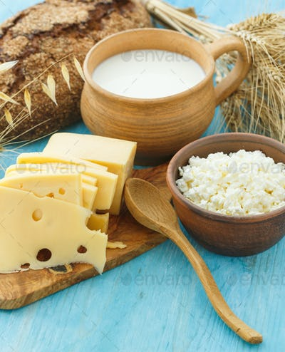 Cottage cheese, milk, bread and cheese on a wooden background