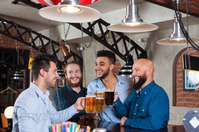 Man Group In Bar Clink Glasses Toasting, Drinking Beer Hold Mugs, Mix Race Cheerful Friends Wear