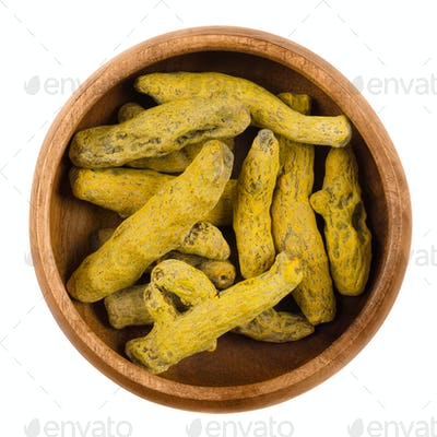 Processed turmeric rhizomes in a wooden bowl over white
