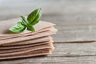 Raw lasagna sheets and basil leaves