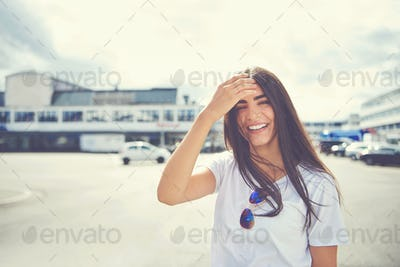 Laughing woman fixes her hair outside