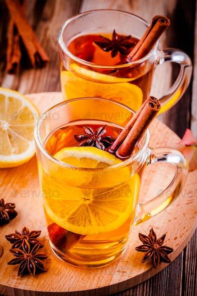 hot tea with lemon, anise and cinnamon in glass mugs