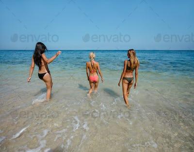 Three young women walking in the sea