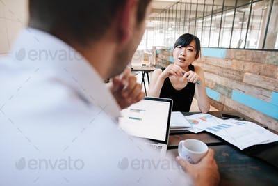 Two businesspeople discussing work in office