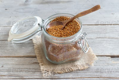 Raw brown millet in a glass jar