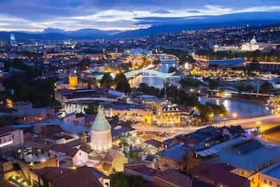 Scenic Top View Of Tbilisi Georgia In Evening Lights Illuminatio