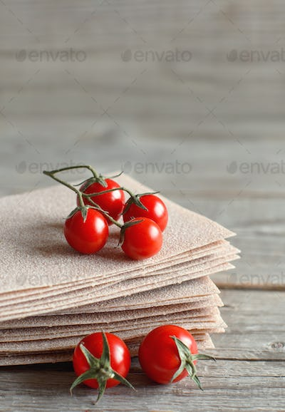 Raw lasagna sheets and cherry tomatoes