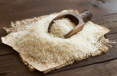 Pile of raw Basmati rice with a spoon