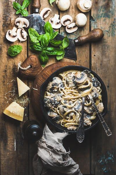 Mushroom pasta spaghetti in iron pan served with parmesan, basil