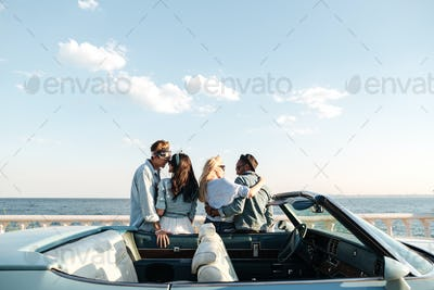 Back view of two couples standing and hugging near car