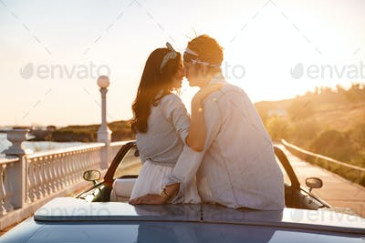 Couple sitting and kissing in car on sunset