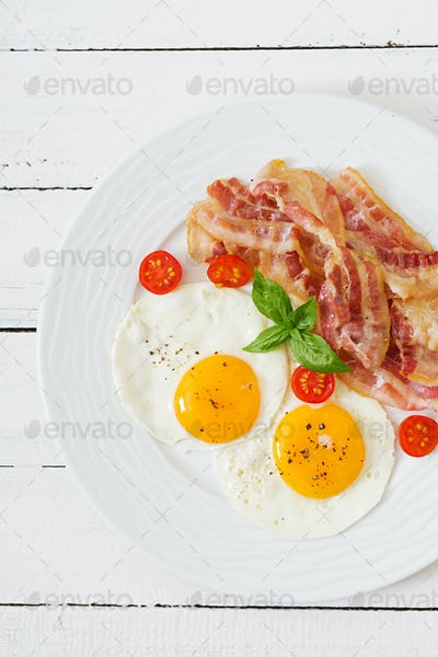 English breakfast - fried egg, tomatoes and bacon. Top view.