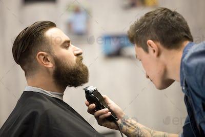 Young man getting beard grooming at barbershop