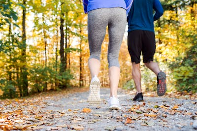 Legs of runners outside in sunny autumn forest