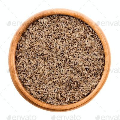 Caraway seeds in a wooden bowl over white