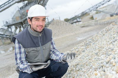 Portrait of worker checking stone in quarry