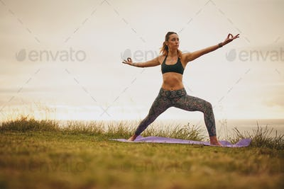 Fit young woman doing yoga on cliff