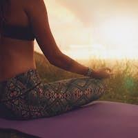 Female sitting in lotus yoga pose on exercise mat