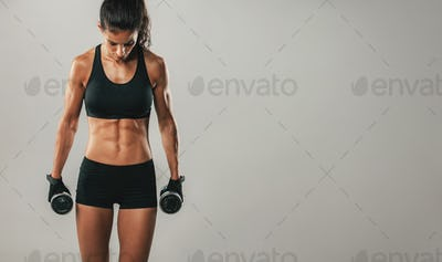 Attractive woman holding dumbbells facing downward
