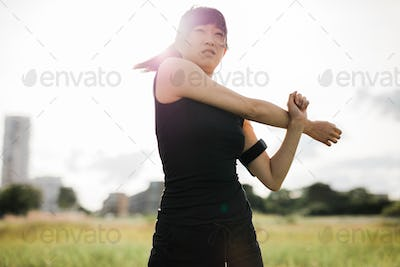 Fit young woman stretching arms at park