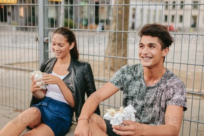 Young man and woman sitting outdoors and smiling.