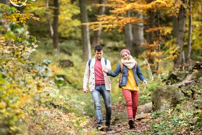 Beautiful couple on a walk in sunny autumn forest