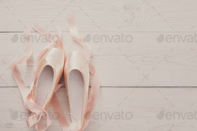 Pink ballet pointe shoes on white wood background