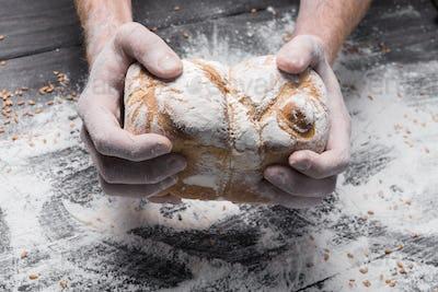 Bakery concept background. Hands hold bread loaf