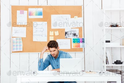 Young tired businessman sitting at the office with laptop
