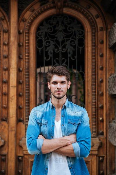 Handsome man standing in front of the beautiful wooden door