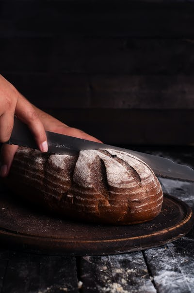 Close-up of baker hands cutting fresh bread from oven