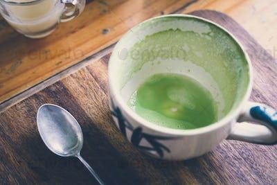Empty matcha latte green tea cup on a wooden board