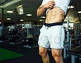 Athletic man showing abdominal muscles in gym