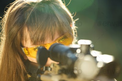 Girl with a gun for trap shooting and shooting glasses aiming at