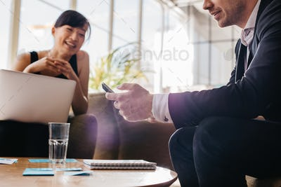 Young business man using mobile phone in meeting