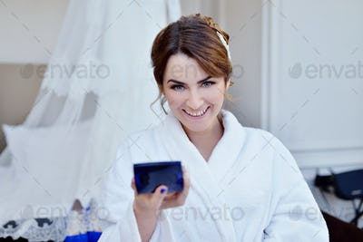 Beauty bride in dressing gown with bridal makeup indoors